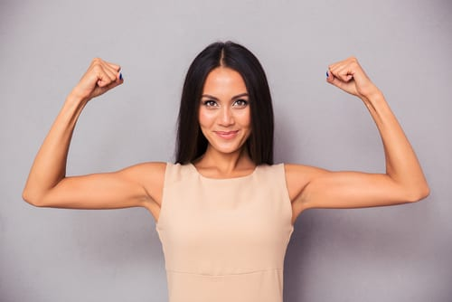 Portrait of a happy elegant woman showing her biceps on gray background-img-blog