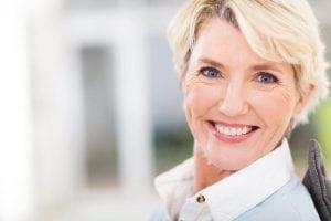 Older woman in white shirt smiling at camera