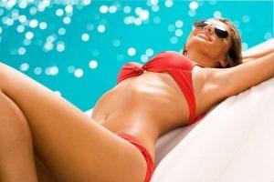 Woman in red bikini laying by pool