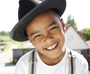 little boy smiling showing his ears under a hat