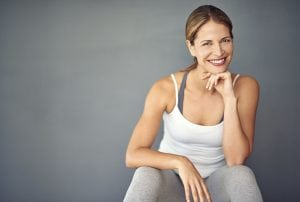 woman sitting and smiling in work out clothes