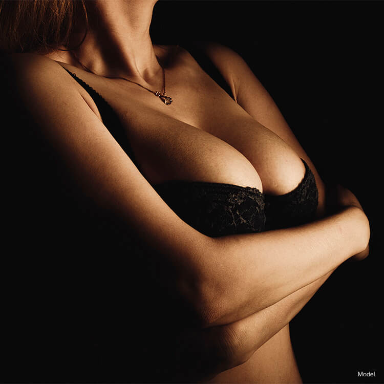 Woman in black bra with arms crossed