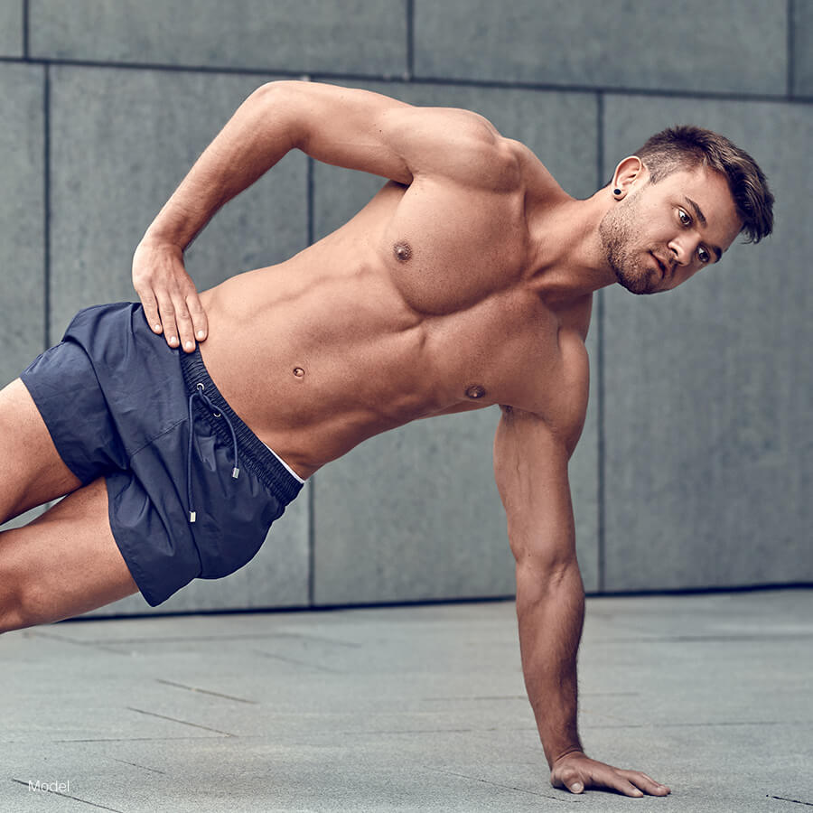 Fit man doing one handed plank