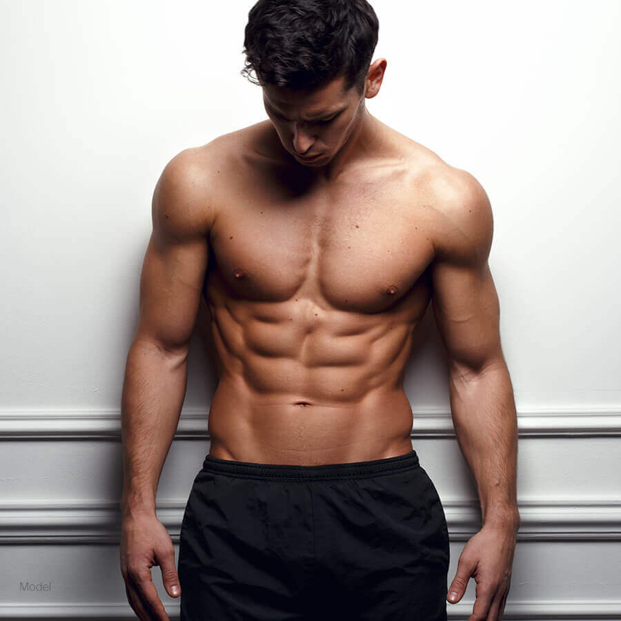 Fit man leaning on wall