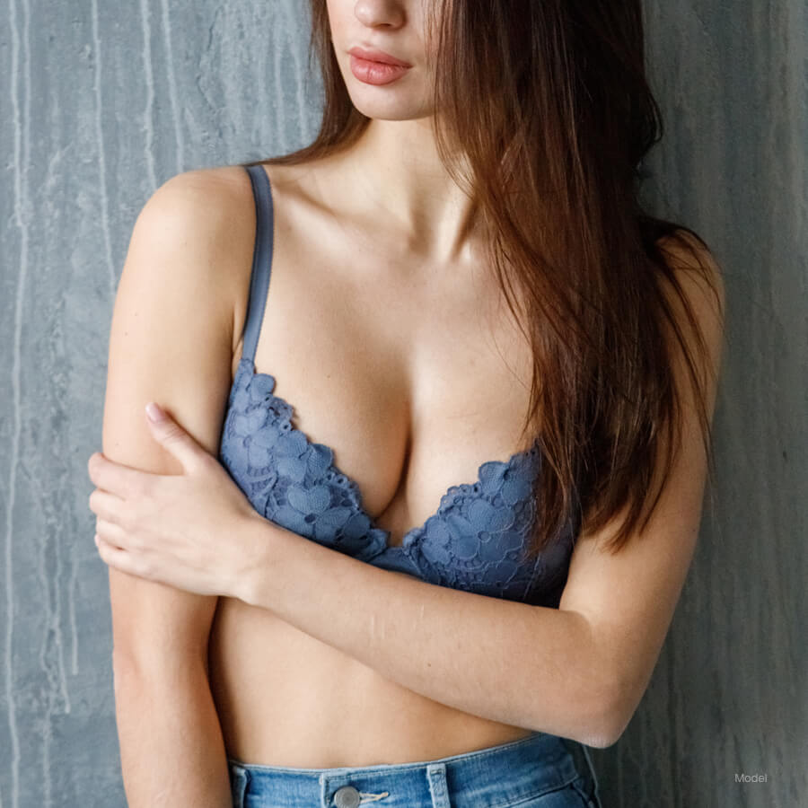 Model in blue holding arm