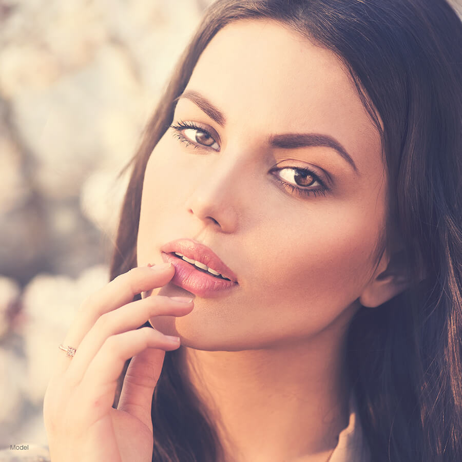 model posing with hand on lip